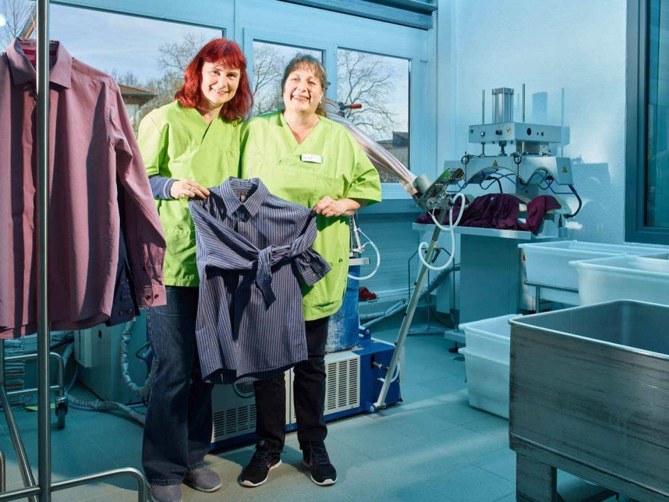 Zwei Mitarbeiterinnen vor den Bügelmaschinen