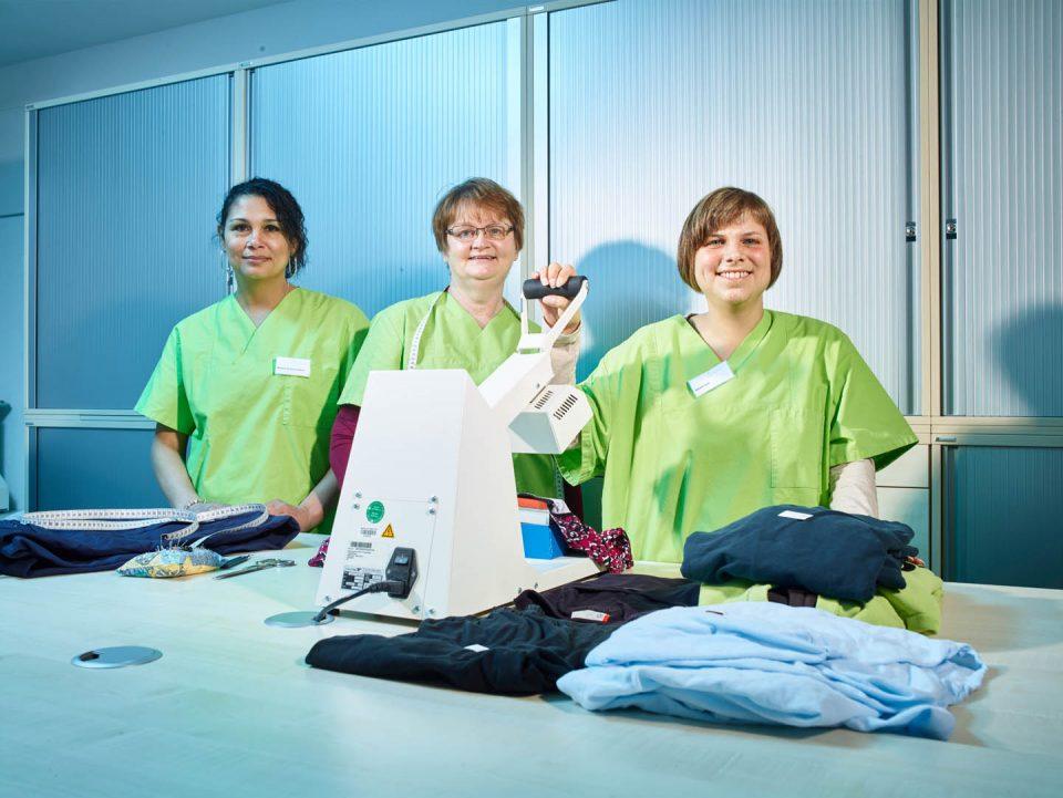 Drei Mitarbeiterinnen bei der Wäschekennzeichnung